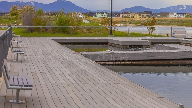 有木甲板的Panorama俯视在象草的岸之外的湖和长凳房子 库存照片