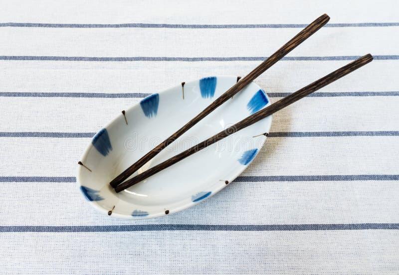 有木筷子的中国汤面碗在镶边法布里 库存照片