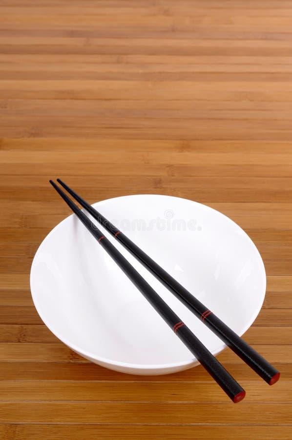 有木筷子的白色空的饭碗在竹背景 免版税库存图片