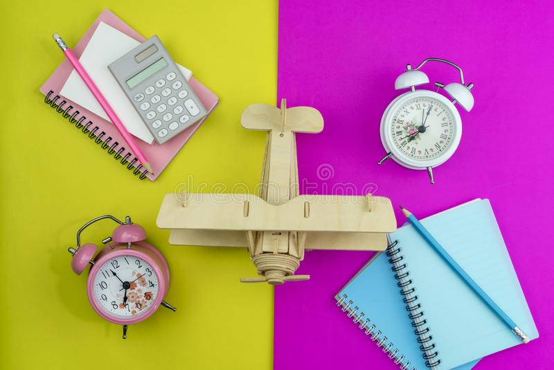 有木飞机、企业白皮书笔记、计算器和铅笔的新的闹钟在纸的颜色背景 库存图片