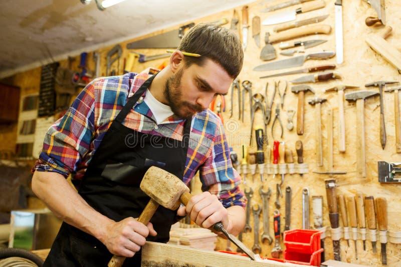 有木头、锤子和凿子的木匠在车间 库存照片
