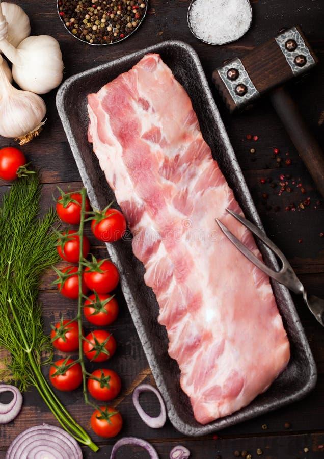 有未加工的排骨的塑料在木背景的盘子在砧板和葡萄酒肉叉子和刀子 新鲜的蕃茄和红色 免版税库存图片