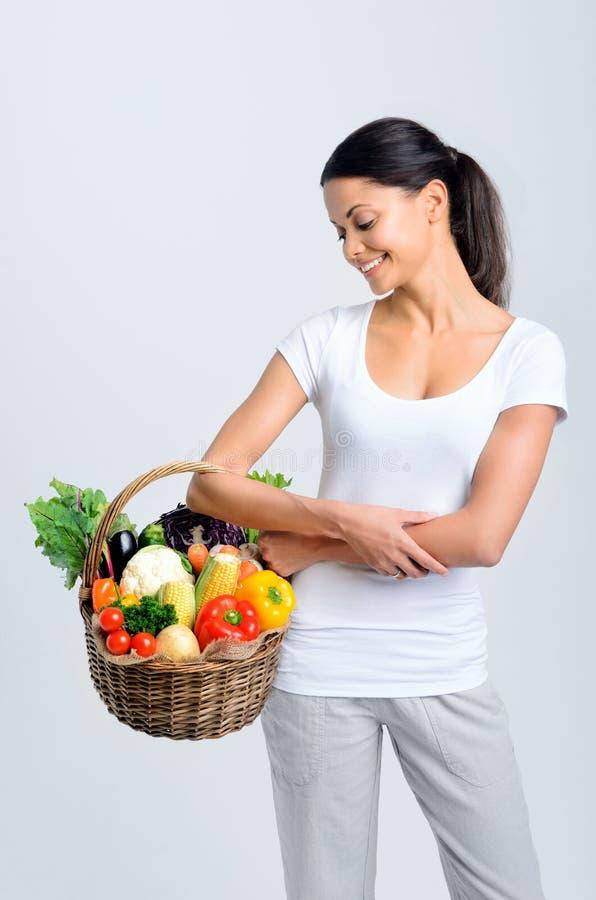 有未加工的新鲜农产品的妇女在篮子 免版税图库摄影