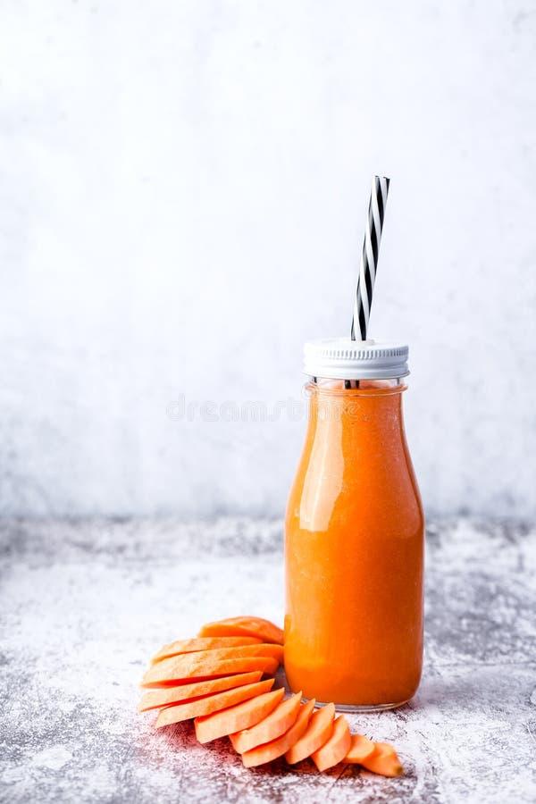有未加工的红萝卜圆滑的人的,右边一个玻璃瓶 免版税库存照片