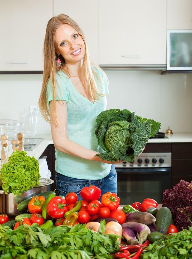 有未加工的蔬菜的快乐的美丽的妇女 库存照片