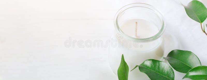 有机化妆用品健康白色蜡烛的长的横幅在玻璃与绿色叶子的瓶子新树枝在木背景 温泉 库存照片