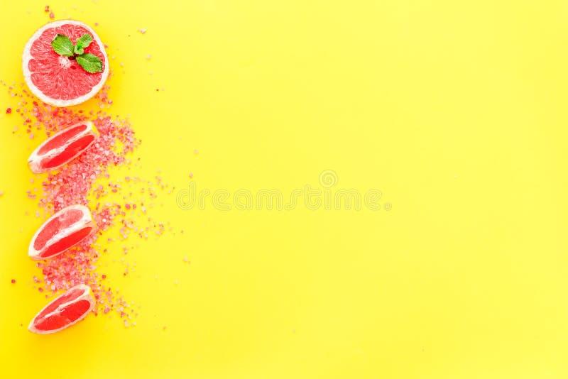 有机化妆用品用自创温泉的葡萄柚与盐和新鲜水果在黄色背景顶视图大模型 图库摄影