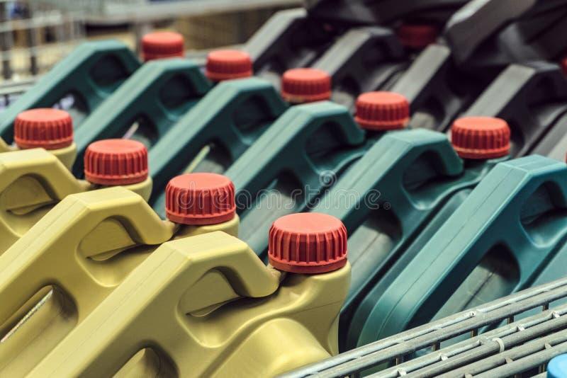 有机器润滑油的色的塑料罐头 在板台安置的罐行  免版税库存照片