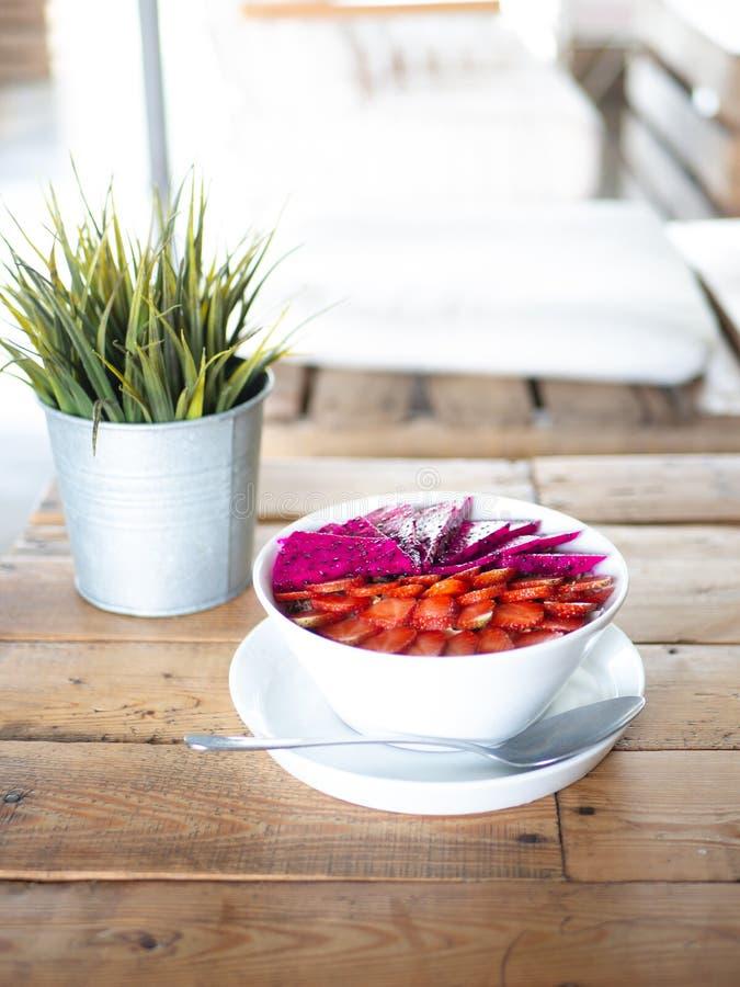 有机圆滑的人碗用在木表上的新鲜水果与明亮的光 库存图片
