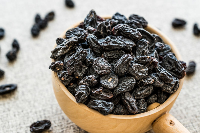 有机干葡萄干或葡萄在木杓子 免版税库存图片