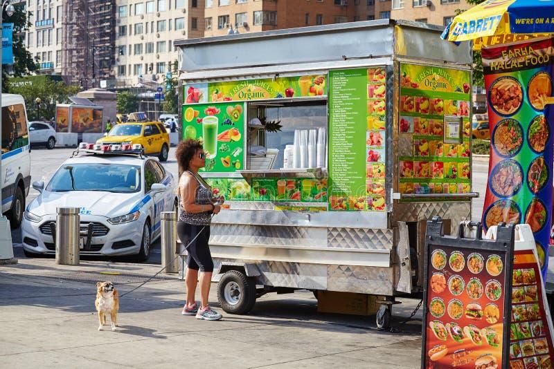 有机新鲜的汁液推车的一名顾客停放了在哥伦布圈子 免版税库存照片