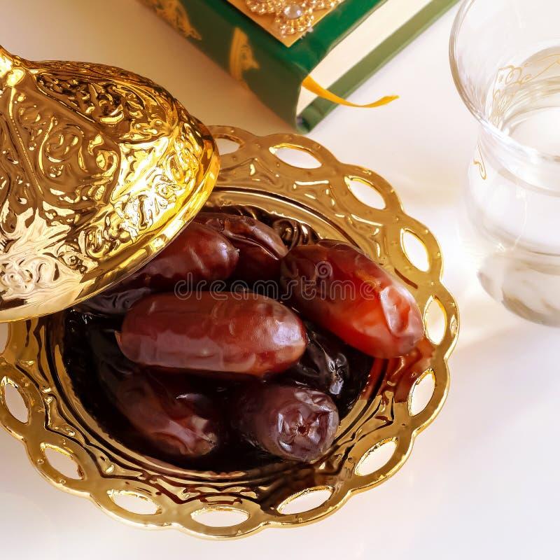 有机日期阿拉伯金黄板材、杯子纯净的饮用水和古兰经书 r r 图库摄影