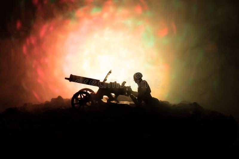 有机枪的人在夜、火爆炸背景或者军事剪影里与在战争雾天空背景,世界W的场面战斗 免版税库存图片