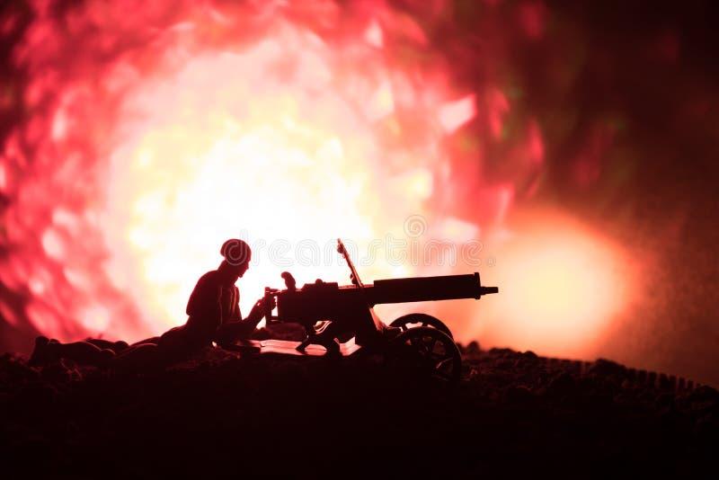 有机枪的人在夜、火爆炸背景或者军事剪影里与在战争雾天空背景,世界W的场面战斗 图库摄影