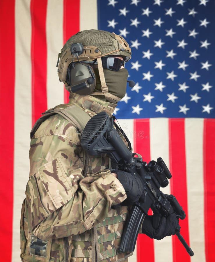 有机枪的美国战士在手上和在背景的美国国旗 免版税库存照片