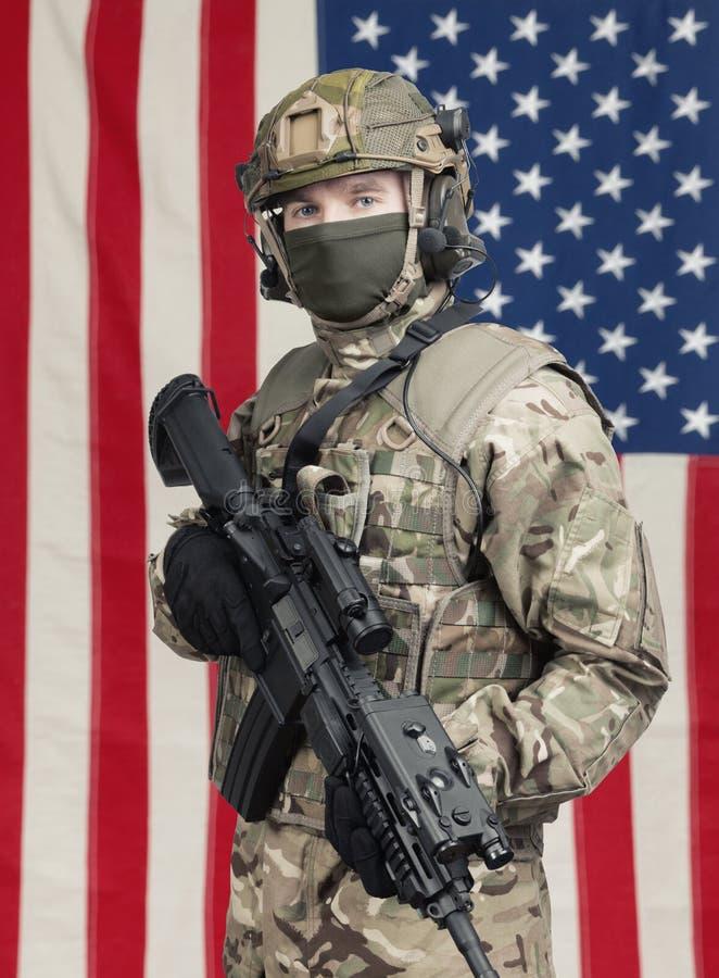 有机枪的美国战士在手中和在背景的美国国旗 库存图片