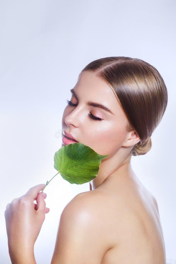有机的化妆用品 与绿色叶子、概念护肤的或有机化妆用品的美丽的妇女面孔画象 免版税库存图片