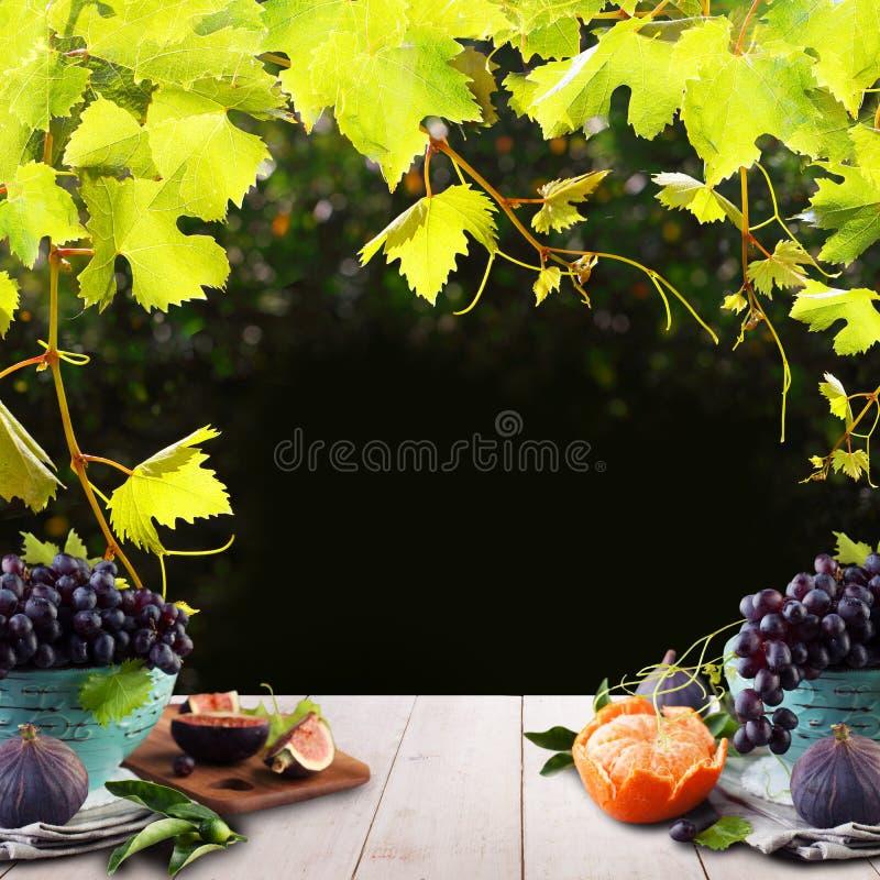 有机食品背景用果子、绿色葡萄叶子和白色木桌 皇族释放例证