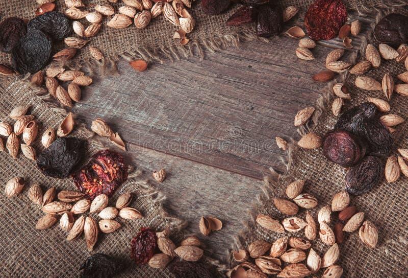 有机食品amonds,葡萄干,杏干,干蕃茄,修剪,烘干了在木书桌的果子 食物混合背景,顶视图, 库存图片