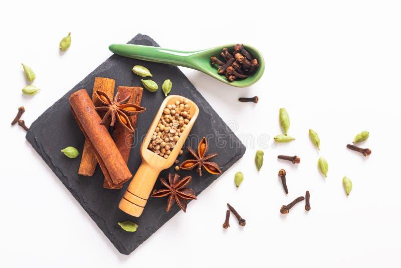 有机香料肉桂条、豆蔻果实荚、八角和芫荽子的异乎寻常的草本食物概念混合在黑色 免版税库存图片
