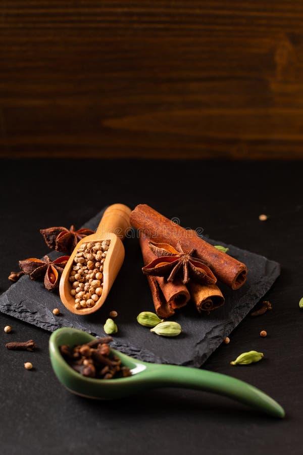 有机香料肉桂条、豆蔻果实荚、八角和芫荽子的异乎寻常的草本食物概念混合在黑色 库存照片