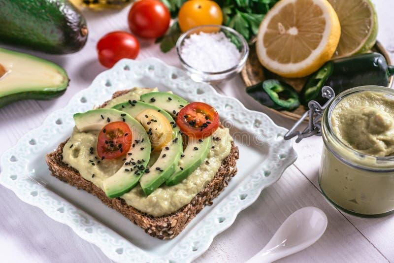 有机鳄梨调味酱捣碎的鳄梨酱鲕梨传播和切片用新鲜的西红柿和黑芝麻 健康饮食早餐概念 库存图片