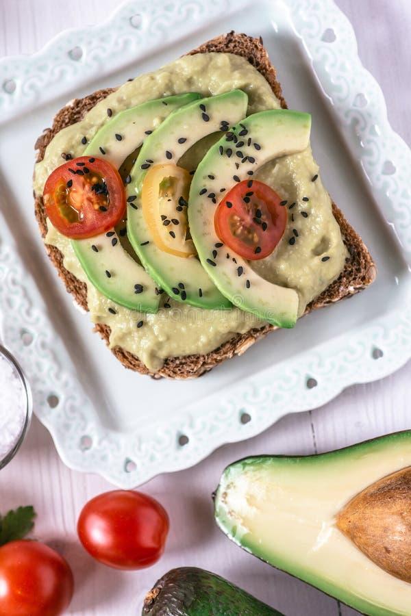 有机鳄梨调味酱捣碎的鳄梨酱鲕梨传播和切片用新鲜的西红柿和黑芝麻 健康饮食早餐概念 免版税库存照片