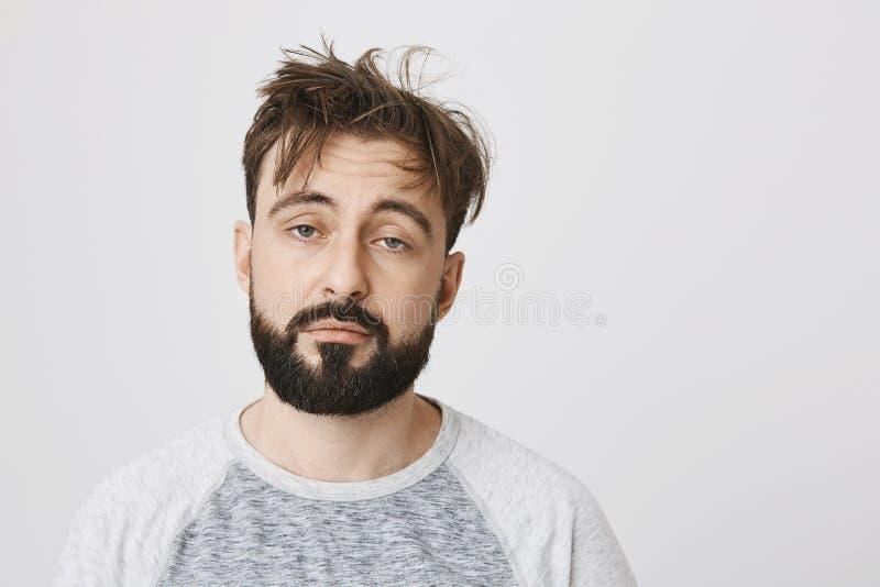 有杂乱头发和阴沉的微笑的不满意的困人,站立在灰色背景 在少量以后的早晨喝可以是 免版税图库摄影