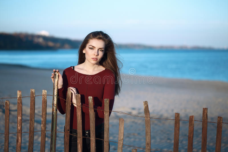有杂乱长的头发的沉思哀伤的孤独的白种人年轻美丽的妇女在室外有风秋天秋天的天在岸海滩 图库摄影