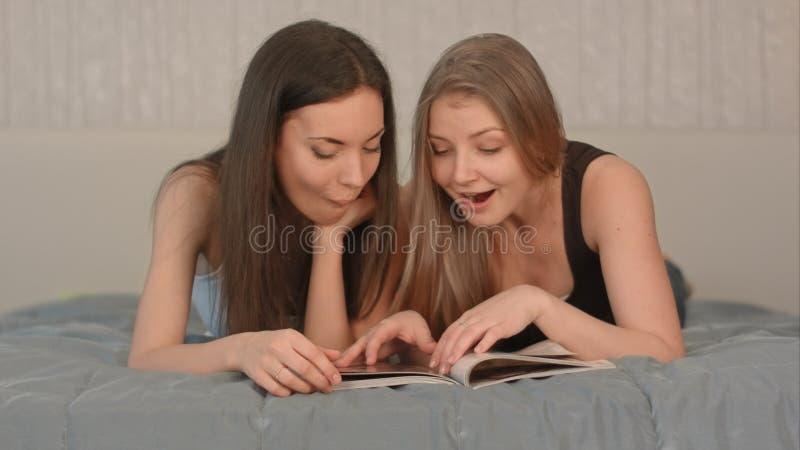 有杂志的两名美丽的妇女在卧室 免版税库存图片