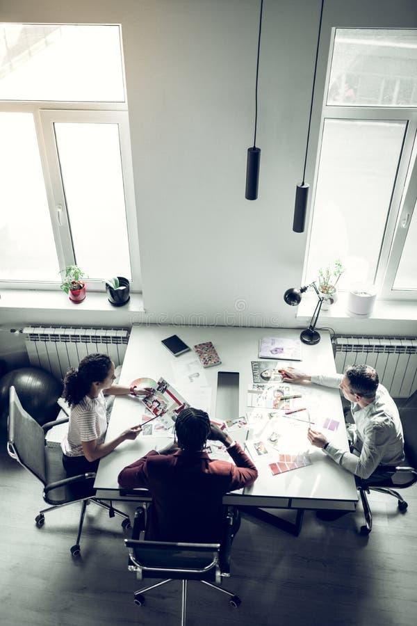 有杂志的职员坐在桌上和讨论 库存图片