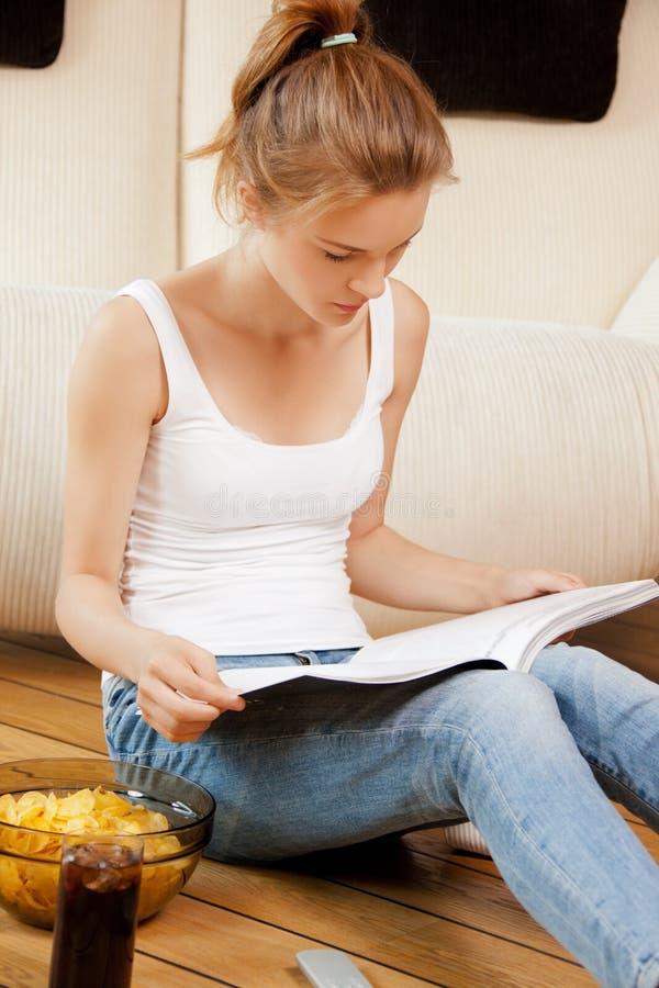 有杂志的镇静和严肃的十几岁的女孩 免版税图库摄影