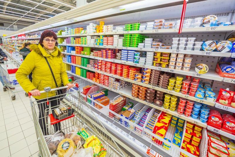 有杂货推车的美丽的成熟妇女在超级市场选择一个家庭的产品 免版税库存图片