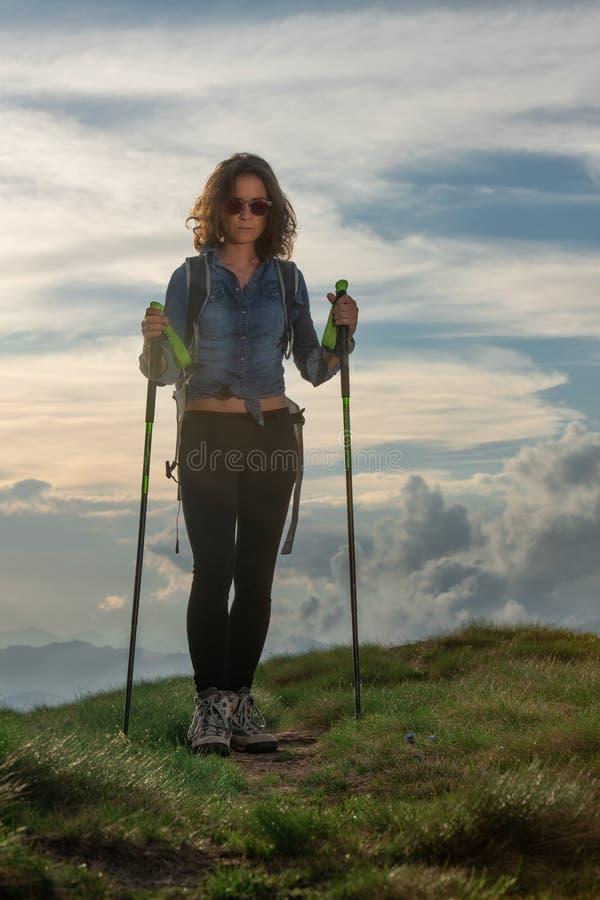 有杆的美丽的女孩在小山的一次远足期间 库存照片