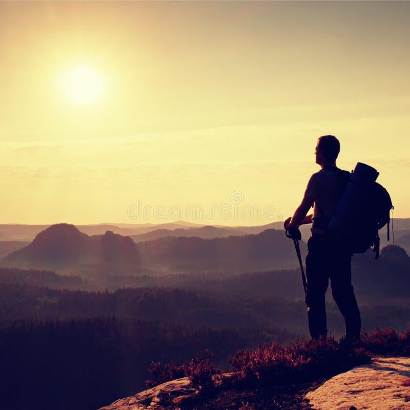 有杆的高背包徒步旅行者在手中 在山的晴朗的破晓 有大背包的远足者在有薄雾的谷上的岩石观点 库存图片