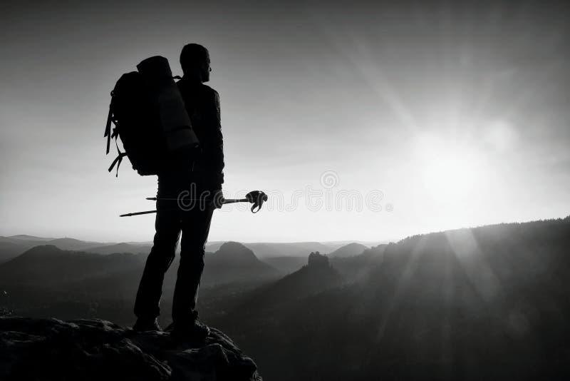 有杆的高背包徒步旅行者在手中 在落矶山脉的晴朗的远足天 有大背包立场的远足者在mis上的岩石观点 免版税库存照片