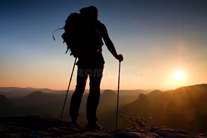 有杆的高背包徒步旅行者在手中 在落矶山脉的晴朗的远足天 有大背包立场的远足者在mis上的岩石观点 库存图片