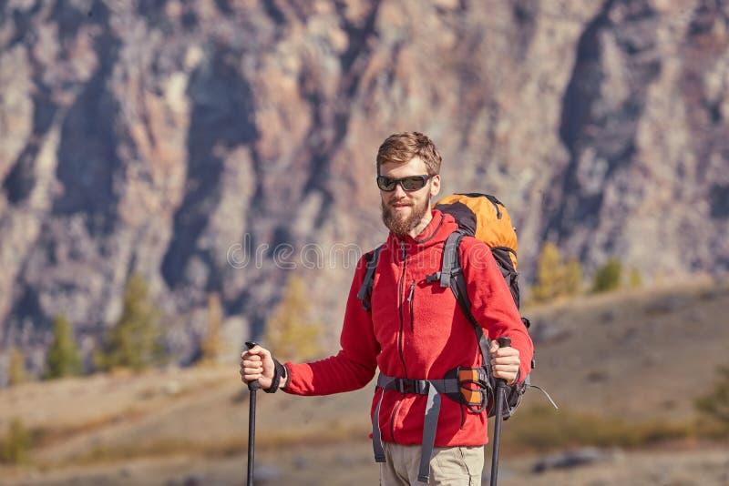 有杆的高背包徒步旅行者在手中 免版税库存照片