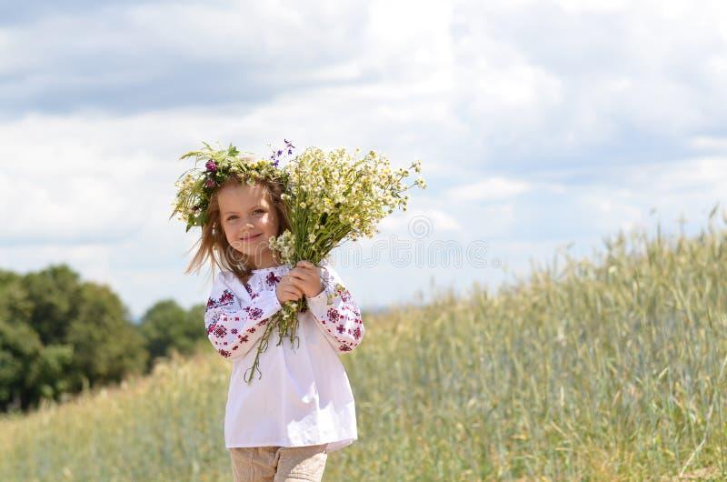 有束的美丽的微笑的女孩野花 免版税库存图片