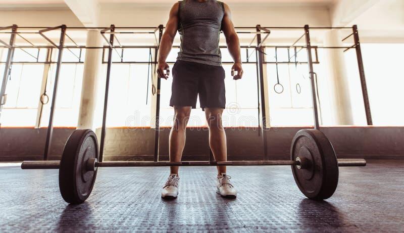 有杠铃的人在健身俱乐部 免版税库存图片