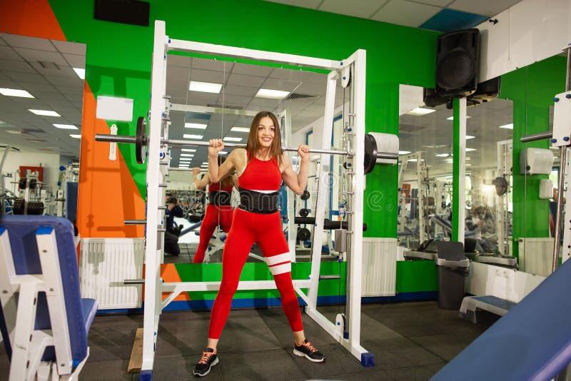 有杠铃的健康年轻女人,制定出行使与大量的重量的女运动员在健身房 库存照片