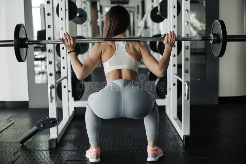 有杠铃的可爱的年轻体育妇女 做蹲坐 r 免版税库存照片
