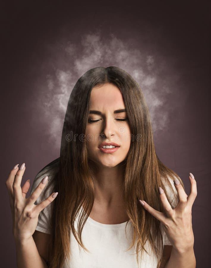 有来自她的头的烟的愤怒的女孩 免版税库存图片