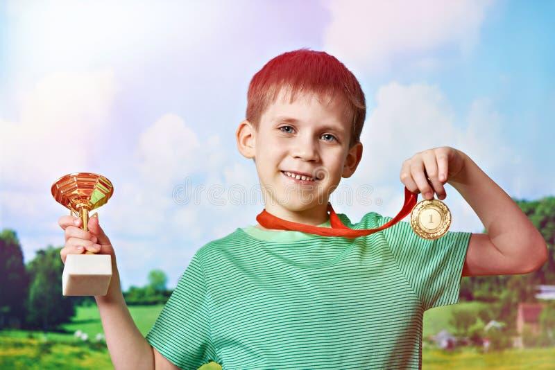 有杯子和奖牌的男孩优胜者在自然 免版税库存图片