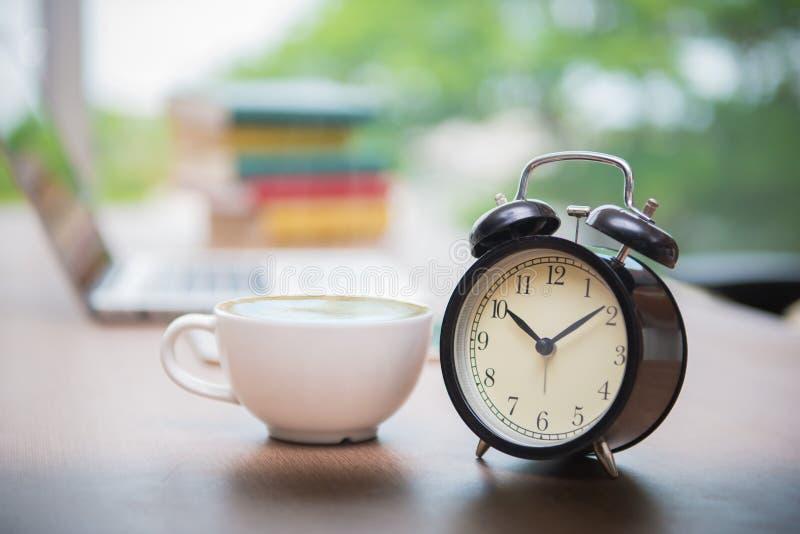 有杯子的减速火箭的闹钟在桌上的热奶咖啡在办公室, Cof 免版税库存图片