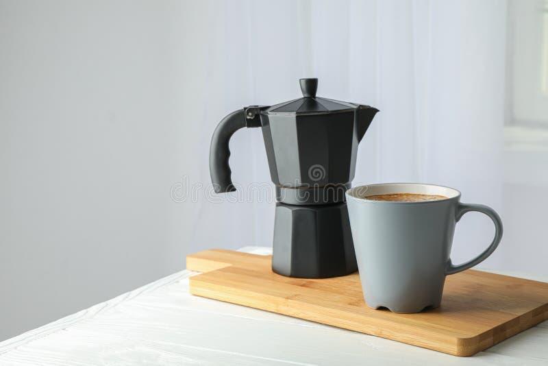 有杯子的切板新鲜的咖啡和咖啡壶在白色桌上反对轻的背景 免版税图库摄影