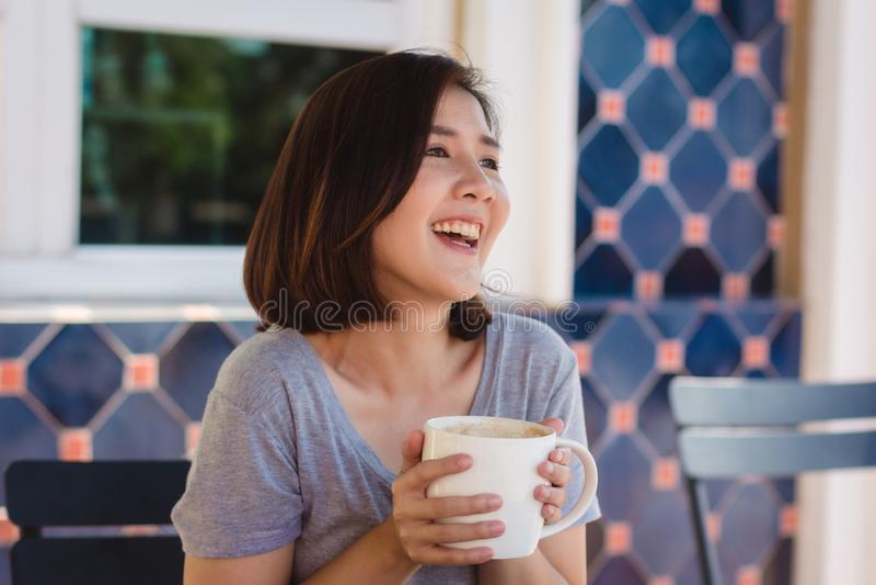 有杯子的在手上喝咖啡的愉快的年轻亚裔女商人画象早晨在咖啡馆 图库摄影