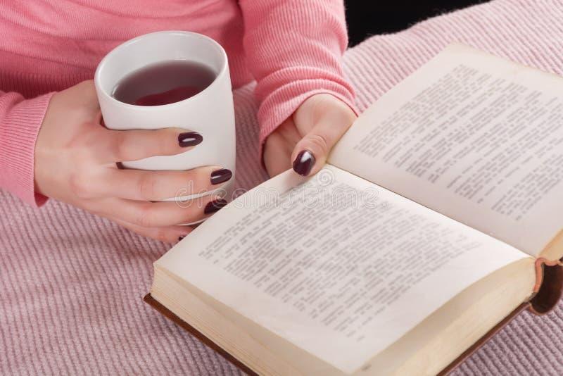 有杯子的女孩热的茶和书在手中在家 桃红色毛衣看书的女性 免版税库存图片
