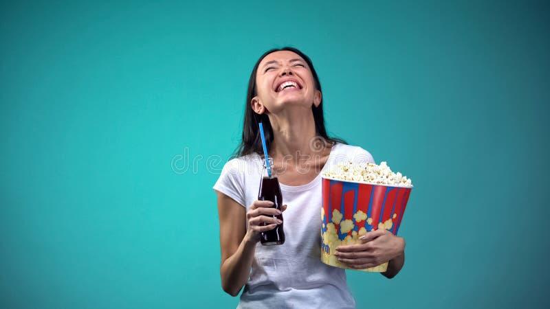 有杯子的妇女玉米花和苏打恳切地笑观看的喜剧,乐趣的 库存图片