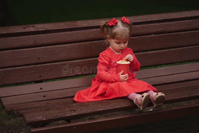 有杯子的小女孩玉米花在公园 库存图片